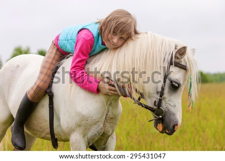 The young girl lies on the white horse back and smiling - stock photo