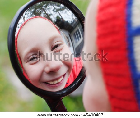 The young girl look in the funhouse mirror on the nature. - stock photo