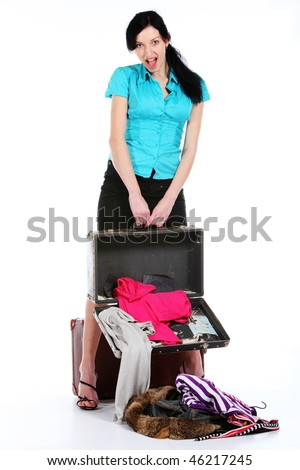 The young girl looks at clothes which has dropped out of the opened old suitcase - stock photo