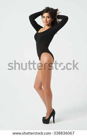 The young girl posing in the studio. Behind her white background. her wearing closed bodysuit and high-heeled shoes. She has gorgeous dark hair and tanned skin. Her white teeth. - stock photo