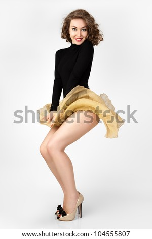 The young girl's skirt flies. Marilyn Monroe style. Fashion photo. - stock photo