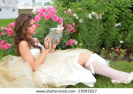 the young girl with book in hand under rosebushes - stock photo