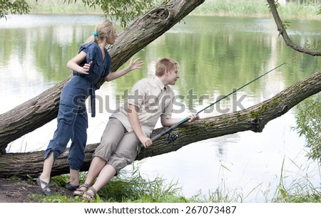The young guy with a rod and the girl shows the size of fish - stock photo