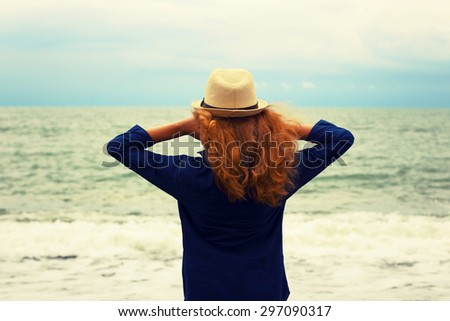 The young lady has a rest on the seashore. The blonde with a fair hair in a hat and jeans. The photo is tinted in a retro style. - stock photo