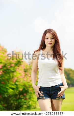 The young long-haired girl in a white vest on park background - stock photo