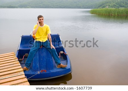 The young man and mobile. By a boat. - stock photo