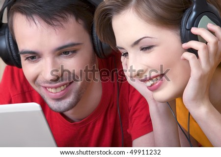 The young man and the girl communicate, having control over musical ear-phones - stock photo