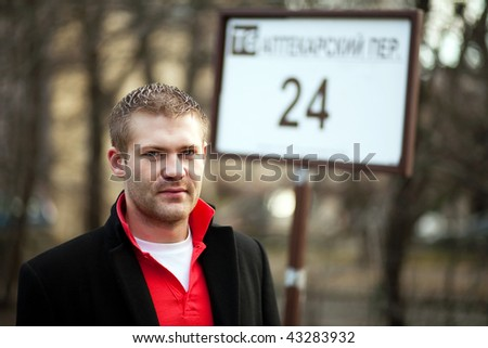 The young man at a bus stop - stock photo