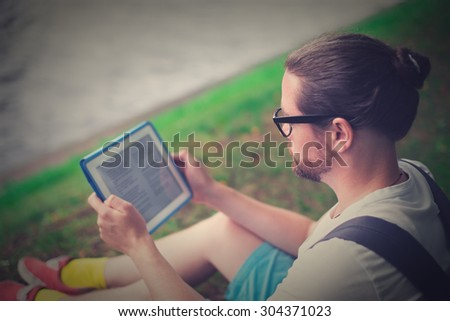 The young man, bearded student sitting in a park on the nature of reading or working on the tablet. - stock photo