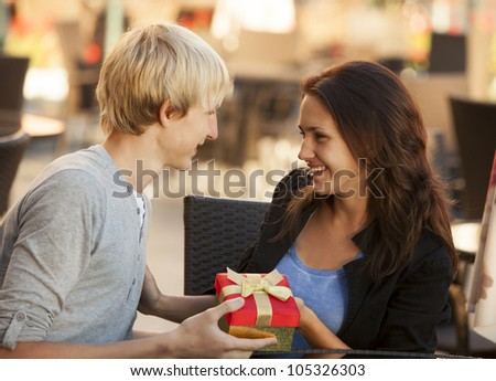 The young man gives a gift to a young girl in the cafe - stock photo