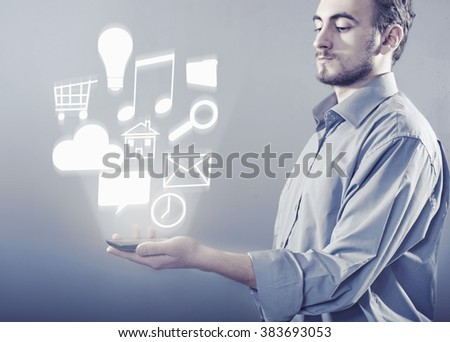 The young man holding a smartphone with holograma of icons - stock photo