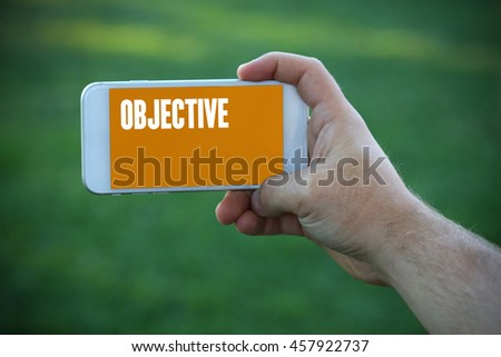 The young man holds the hand Objective by smartphone - stock photo