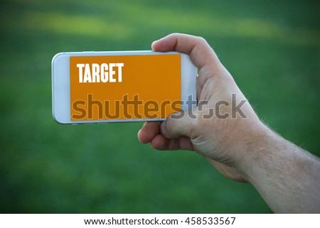 The young man holds the hand Target by smartphone - stock photo