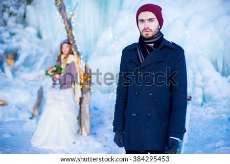 the young man in a coat with a stylish hairdress and with a red butterfly poses near an ice floe in the winter - stock photo