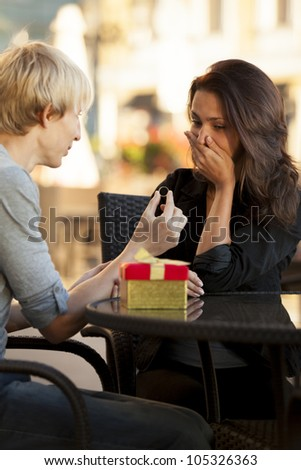 The young man proposes to a young girl in the cafe - stock photo