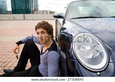 The young man sits near to expensive car - stock photo