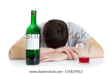 the young man sleeping at a table and a bottle with wine - stock photo