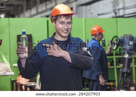 The young man working at the old factory on installation of equipment in a protective helmet - stock photo