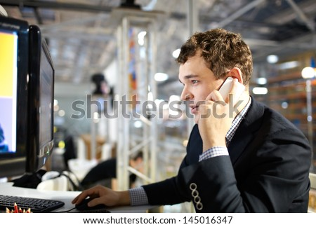 The young man works at a computer and talking on the phone. - stock photo