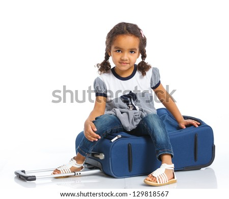 The young mulatto traveler girl with a suitcase. Isolated over white background - stock photo
