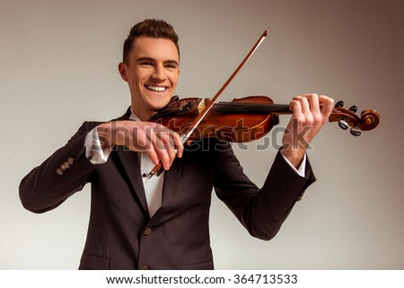 The young musician man playing violin on gray background - stock photo