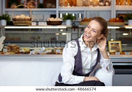 The young nice girl at a show-window with cakes - stock photo
