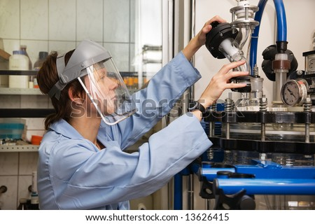 The young nice woman-scientist in protecting mask work with scientific instrument - stock photo