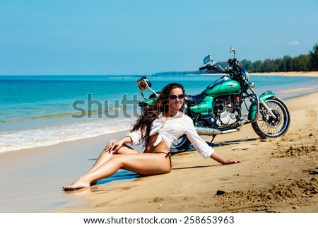 The young sexy girl in a bathing suit on a beach with the motorcycle. - stock photo
