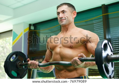 The young sports athlete is engaged in a gym with dumbbells and showing the sound body - stock photo