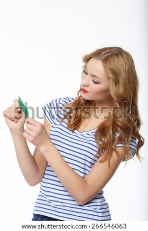 The young thoughtful woman, considers the map of the blank credit, on a white background - stock photo