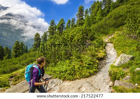 The young woman at one of the mountain trails in the valley Zillertal, in the lush green grass and blue sky, Zillertal Alps, Austria - stock photo