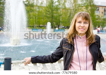 The young woman at the fountain - stock photo