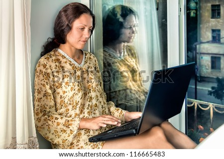 The young woman at the window with a laptop - stock photo