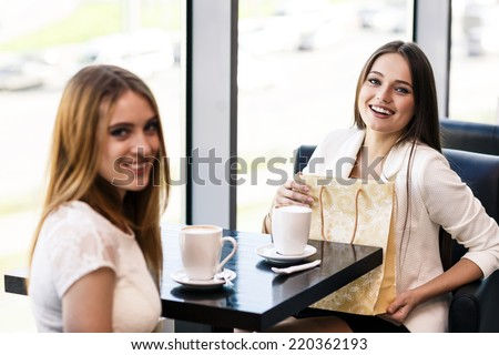 The young woman gives a gift to a young girl in the cafe - stock photo
