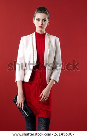 The young woman holding purse on red background - stock photo