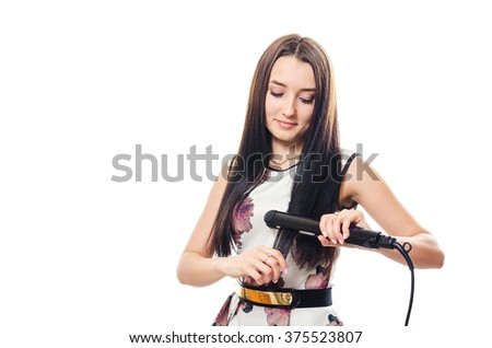 The young woman in a dress irons hair the iron - stock photo