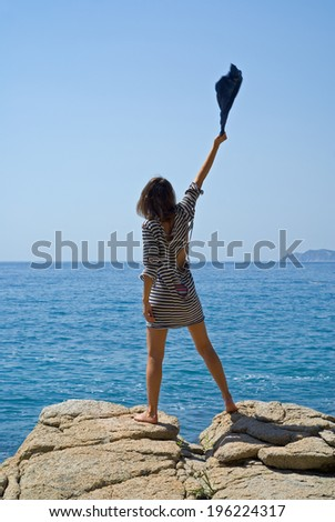 The young woman in old striped vest stands on rock at sea. - stock photo