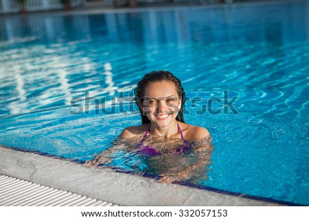 The young woman in the swimming pool - stock photo