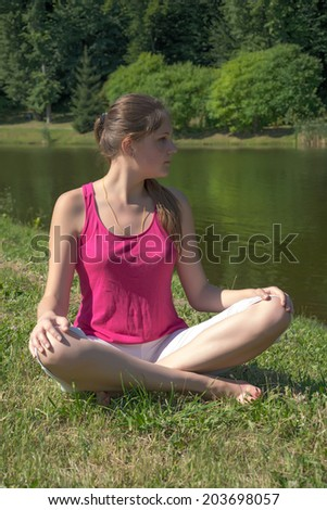 The young woman is engaged in the eastern culture, practicing yoga by the lake - stock photo