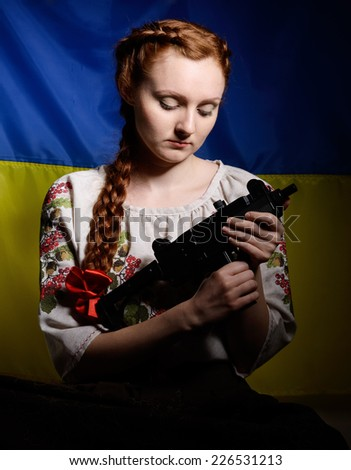 The young woman is holding a gun against the national Ukrainian flag. She is wearing a shirt embroidered. Her red hair are plaited with a red ribbon. - stock photo