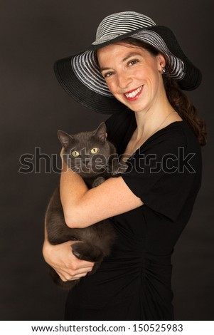 The young woman is holding the cat in her arms - stock photo