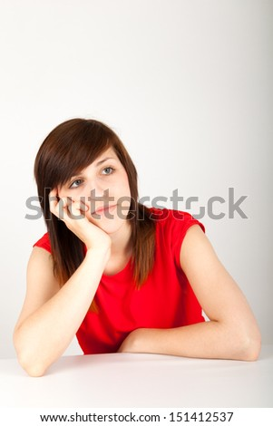 The young woman is sitting bored at a table - stock photo