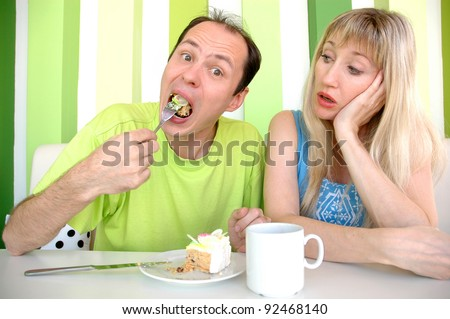 The young woman looks as the man eats a cake - stock photo
