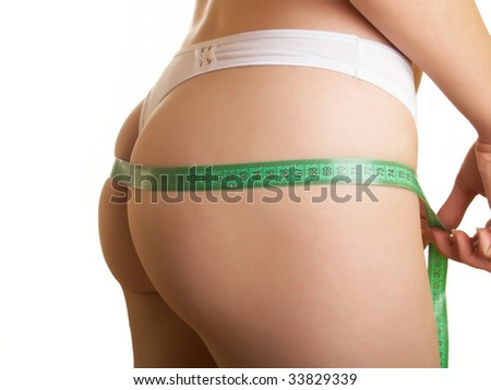 The young woman measures to itself a ass on a white background - stock photo