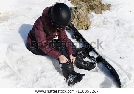 The young woman puts legs in boots for a snowboard, she sit on snow - stock photo