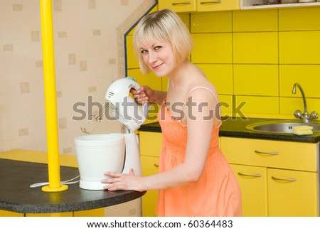 The young woman uses a mixer on kitchen - stock photo