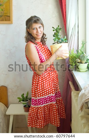 The young woman with a flower at a window - stock photo