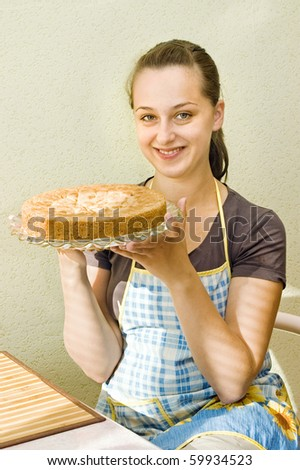 The young woman with a pie in hands, on kitchen - stock photo