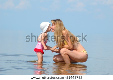 The young woman with the little girl concern with noses on a beach - stock photo
