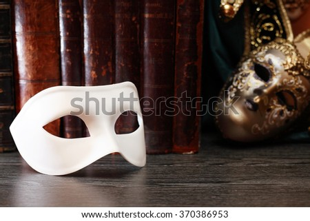Theater concept. Closeup of white classical carnival mask on books background - stock photo